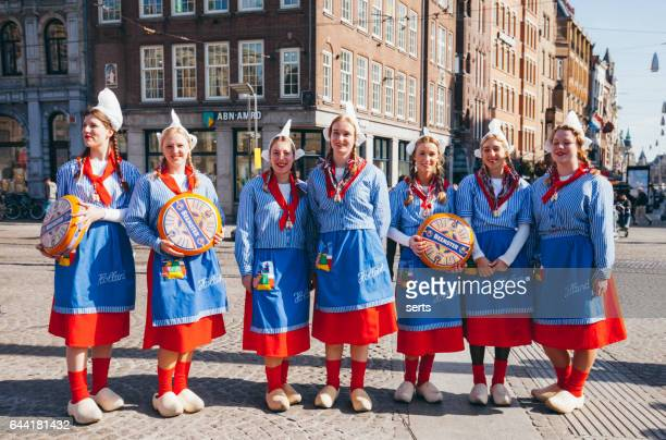 traditional dressed dutch girls on a cheese market - dutch culture stock photos and pictures