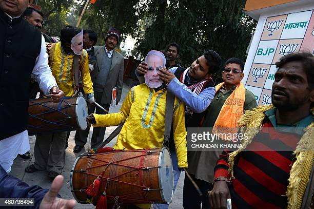 A traditional drummer wears a mask bearing the portrait of Indian Prime Minister Narendra Modi as Bharatiya Janata Party supporters celebrate...