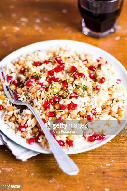 traditional east asian meal. plate of warm salad with couscous, chickpea, pomegranate seeds, lemon zest, almond flakes and dill on a wooden table, selective focus. healthy and organic food option. - black seed oil stock pictures, royalty-free photos & images