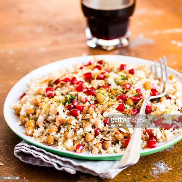 traditional east asian meal. plate of warm salad with couscous, chickpea, pomegranate seeds, lemon zest, almond flakes and dill on a wooden table, selective focus. healthy and organic food option. - couscous marocain photos et images de collection