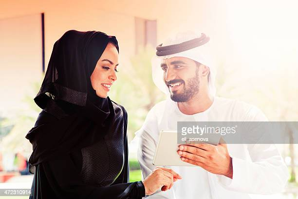 Traditional Emirati young family surfing in Internet