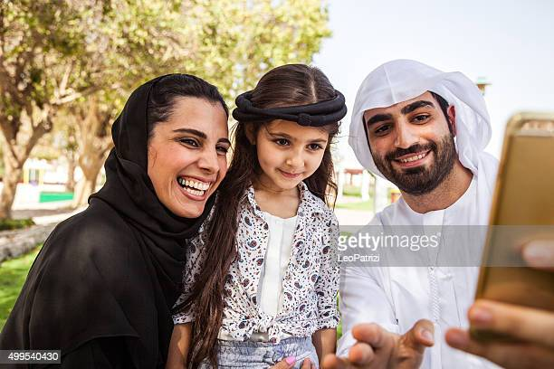 Traditional Emirati young family taking a selfie
