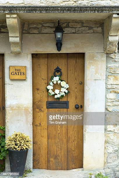 Traditional English oak timber front door of country cottage with flower garland in quaint village of Castle Combe in The Cotswolds UK