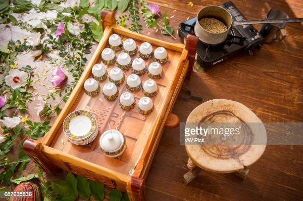 Traditional Ethiopian coffee serving dishware wooden stool flowers and leaves spread on floor