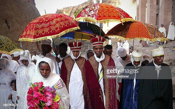 Traditional Ethiopian Orthodox wedding celebration in Lalibela. The Groom and Bride both wear headdresses with regal robes and ornate parasols over...