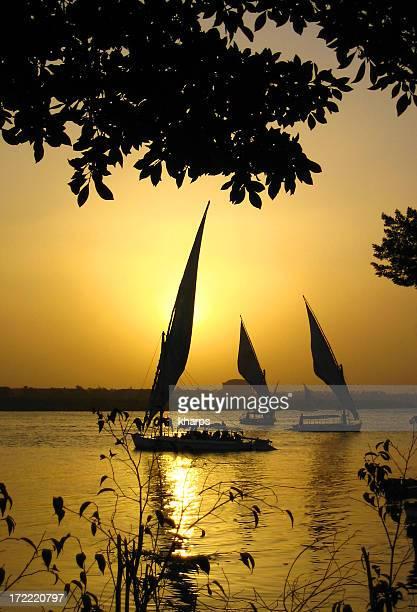 Tradicional excursión en felucca barcos en la puesta de sol sobre el Nilo, cerca de El Cairo