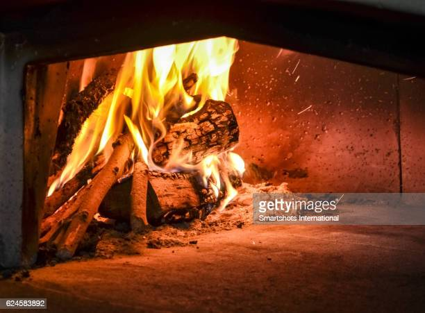 Traditional firewood oven with burning fire ready to cook traditional Italian pizza, bread or bakeries