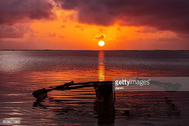 Traditional fisher boat in Zanzibar on a white beach at a beautiful sunrise