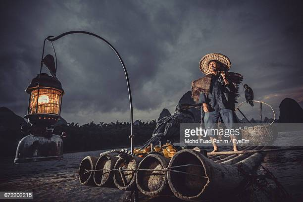 Traditional Fisherman By Cormorants On Wooden Raft Over River Against Cloudy Sky
