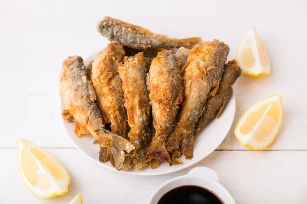 A traditional fisherman dish with lemon. Traditional English or Asian fast food, fried river fish.