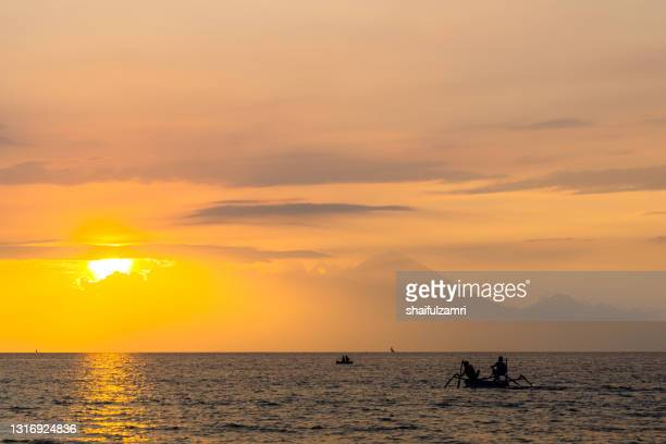 traditional fisherman during majestic sunset in lombok, indonesia - shaifulzamri stock pictures, royalty-free photos & images