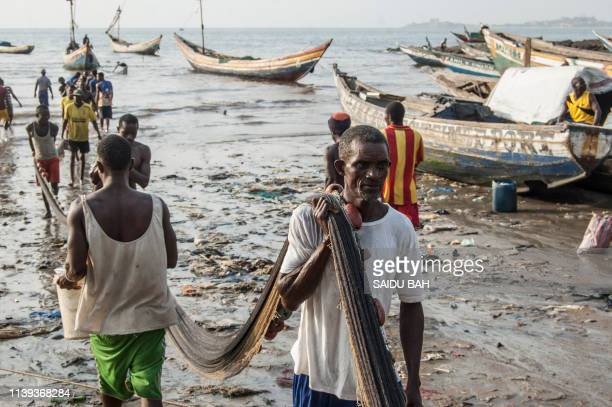 Traditional fishermen carry fish nets to the Goderich Market in Sierra Leone's capital Freetown on April 10, 2019.