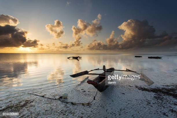 traditional fishing boat in zanzibar with storm clouds at sunrise - zanzibar stock pictures, royalty-free photos & images