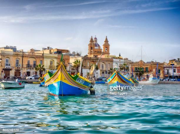 traditional fishing boats at marsaxlokk harbour - marsaxlokk stock pictures, royalty-free photos & images
