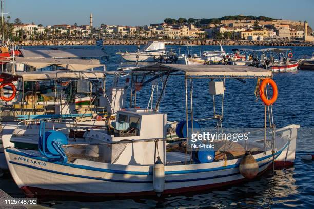 Traditional fishing boats seen docked in the marina of Rethymno the port of the town In the background is the old historic center with the Venetian...