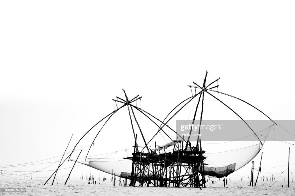 A traditional fishing method still use by fisherman at southern Thailand. The temporary wooden and bamboo structure is built over the sea with hanging fishing net which can be lowered into the sea by meant of human body weight. : Stock Photo