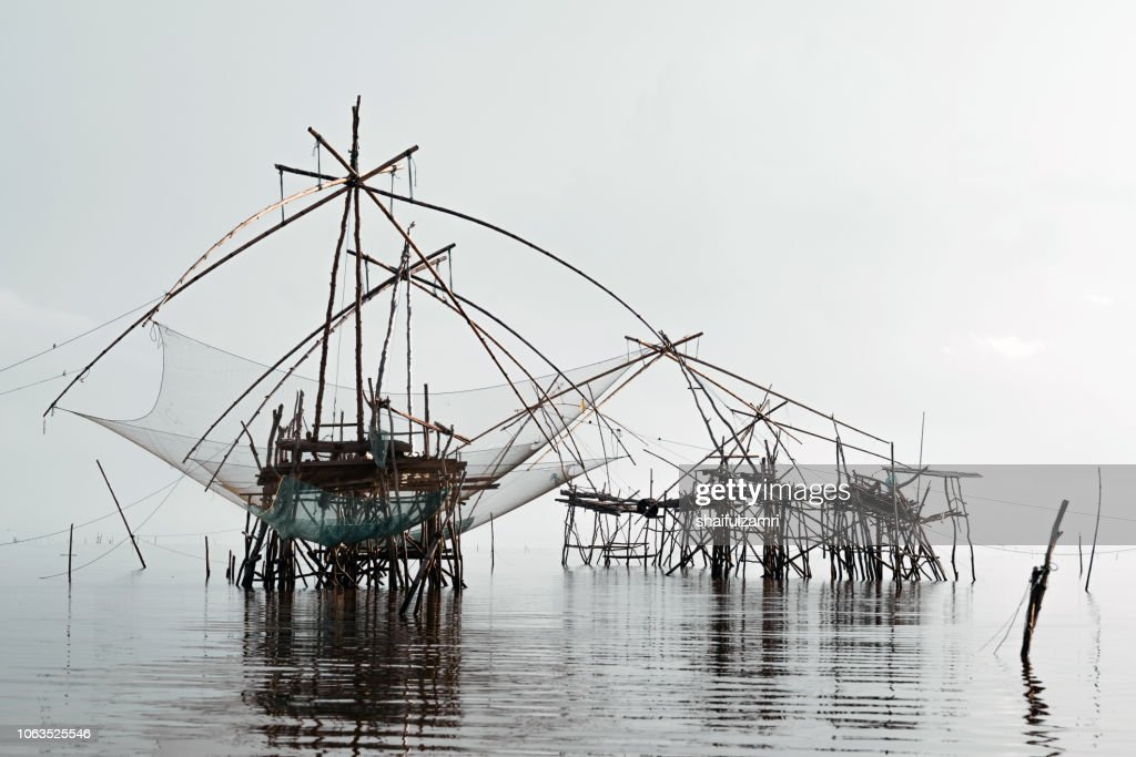 Traditional fishing nets made from bamboo and wood over cloudy sunrise at lake Thale Noi, Phatthalung, Thailand. : Stock Photo