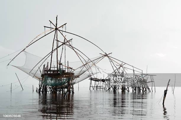 Traditional fishing nets made from bamboo and wood over cloudy sunrise at lake Thale Noi, Phatthalung, Thailand.