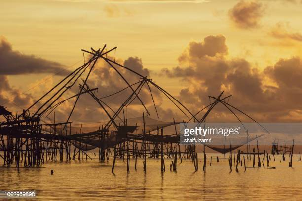 Traditional fishing nets made from bamboo and wood over golden sunrise at Phatthalung, Thailand.