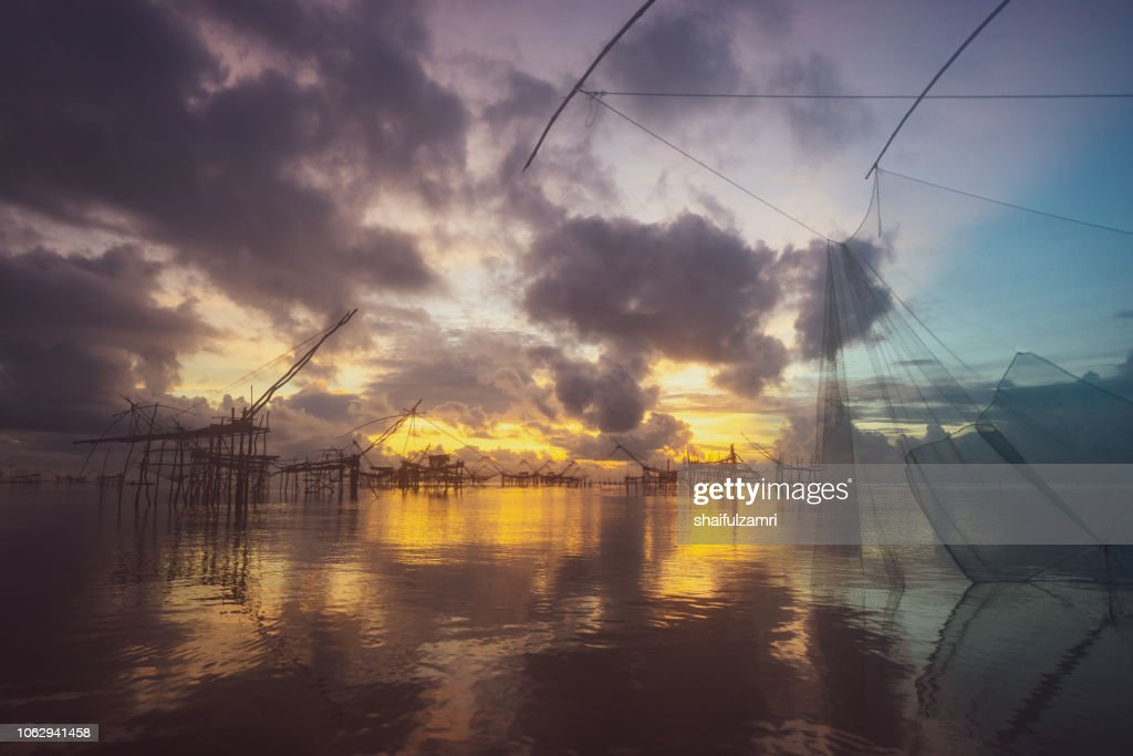 Traditional fishing nets made from bamboo and wood over sunrise at Phatthalung, Thailand. : Stock Photo