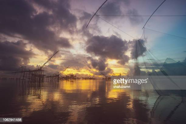 Traditional fishing nets made from bamboo and wood over sunrise at Phatthalung, Thailand.