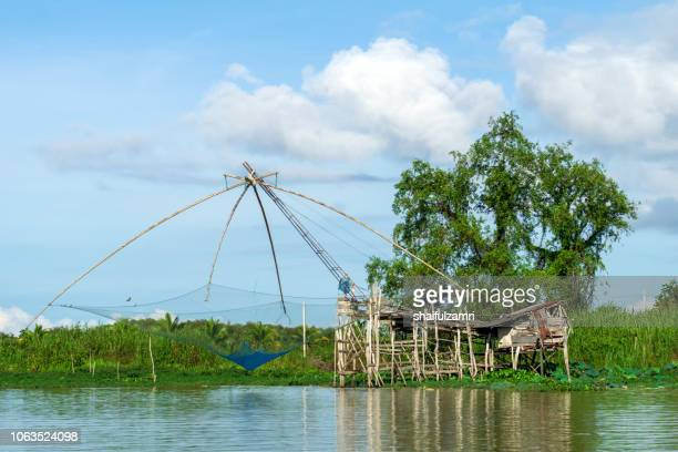 Traditional fishing nets made from bamboo and wood over sunrise at lake Thale Noi, Phatthalung, Thailand.
