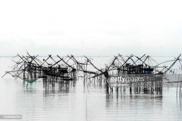Traditional fishing nets over cloudy day at Phatthalung, Thailand.