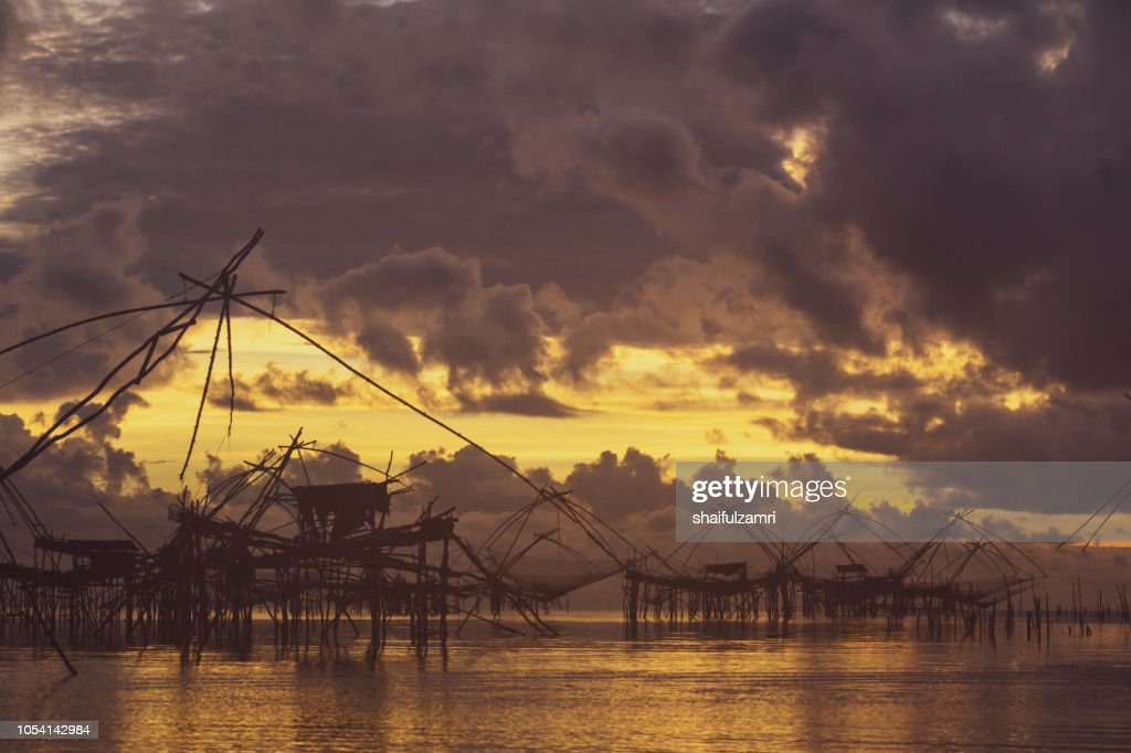 Traditional fishing nets over cloudy sunrise at Phatthalung, Thailand. : Stock Photo