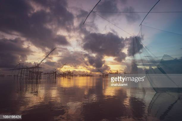 Traditional fishing nets over cloudy sunrise at Phatthalung, Thailand.