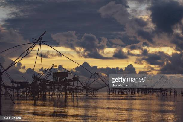 traditional fishing nets over cloudy sunrise at phatthalung, thailand. - shaifulzamri 個照片及圖片檔