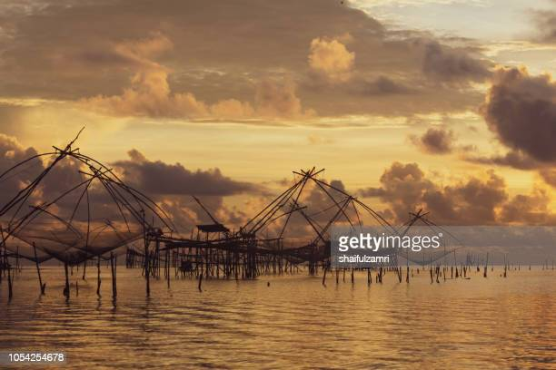 traditional fishing nets over cloudy sunrise at phatthalung, thailand. - shaifulzamri fotografías e imágenes de stock