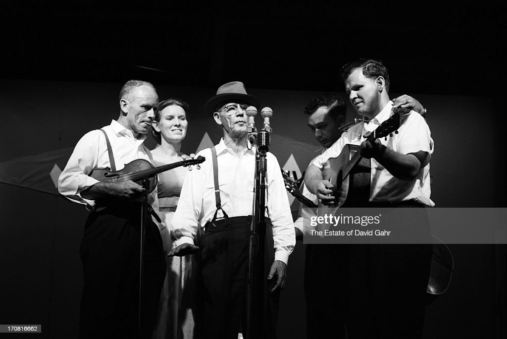 Traditional folk and old-timey musicians including (l-r) fiddler Fred Price, folk singer Jean Ritchie, banjoist, musician and singer Clarence Ashley, guitarist and singer Clint Howard, and guitarist and singer Doc Watson perform at the Newport Folk Festival in July, 1963 in Newport, Rhode Island.
