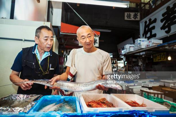 A traditional fresh fish market in Tokyo. Two men, a seller and client holding a long fish for sale.