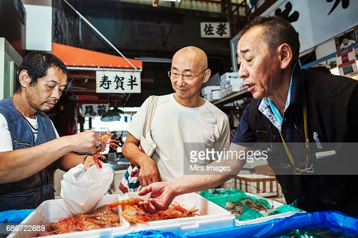 A traditional fresh fish market in Tokyo. Two people selecting shellfish for a customer to buy, filling a bag from boxes of prawns.
