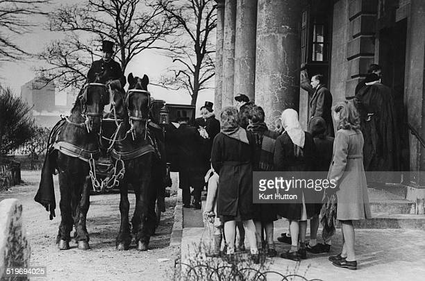 A traditional funeral procession led by four black horses arriving at St Mary's Church Battersea before proceeding to Wandsworth Cemetery The...