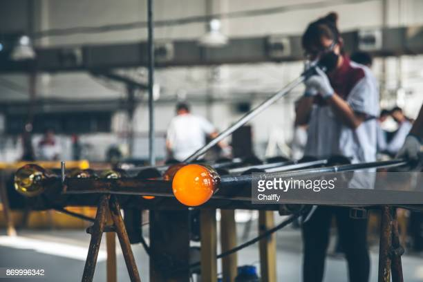 Traditional glassblowing worker blowing glass