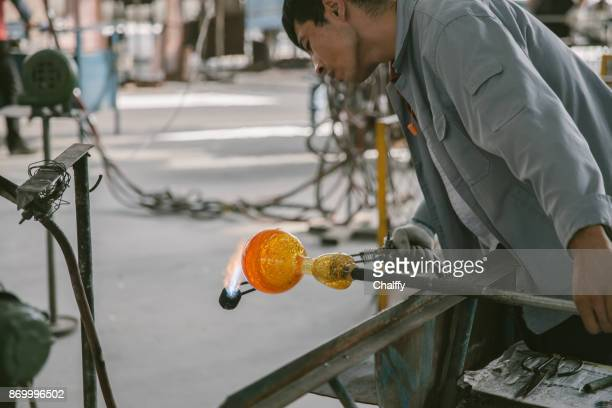Traditional glassblowing worker heating glass