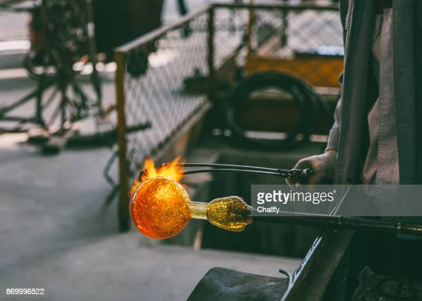 Traditional glassblowing worker heating liquid glass
