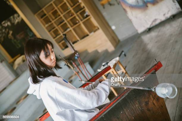 Traditional glassblowing worker shaping glass