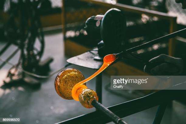 Traditional glassblowing worker shaping liquid glass