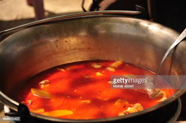 Traditional Goulash soup is cooking in the a cauldron