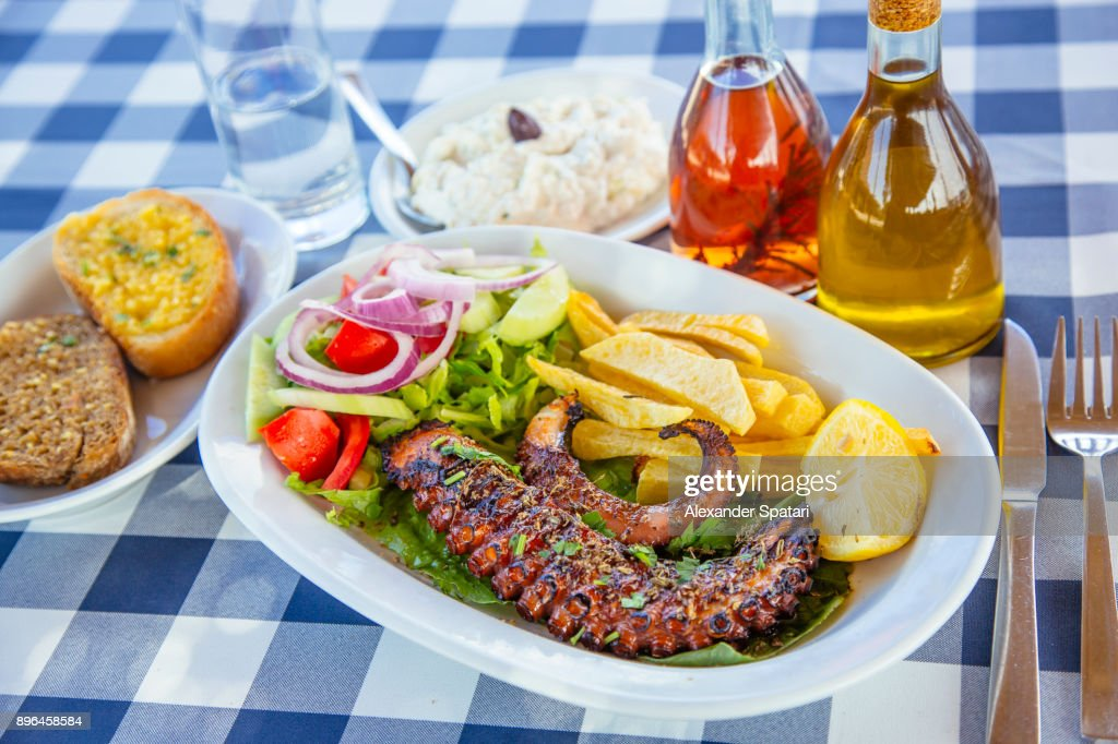 Traditional Greek dinner with grilled octopus and tzatziki : Stock Photo