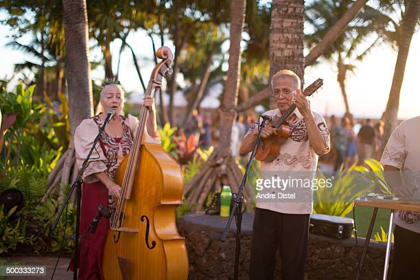 CONTENT] A traditional Hawaiian band is playing traditional Hawaiian songs in a tropical setting on Maui