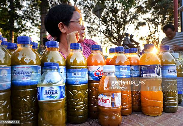 A traditional herbal medicine vendor at the market in Sayan Ubud waits for her customers The drinks are made from tumeric other roots and herbs and...