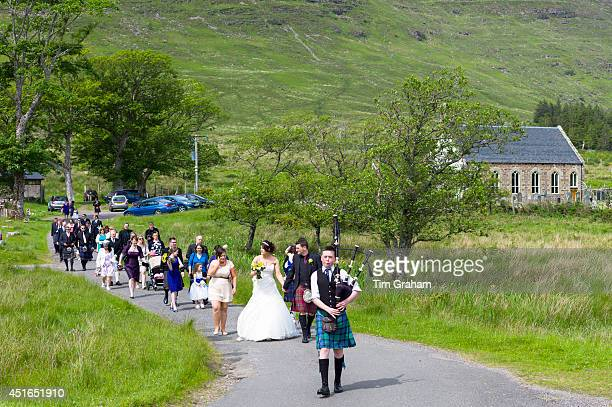 Traditional Highland Scottish wedding with piper leading procession of bride and groom and wedding guests from Clachan Church in to the wedding...