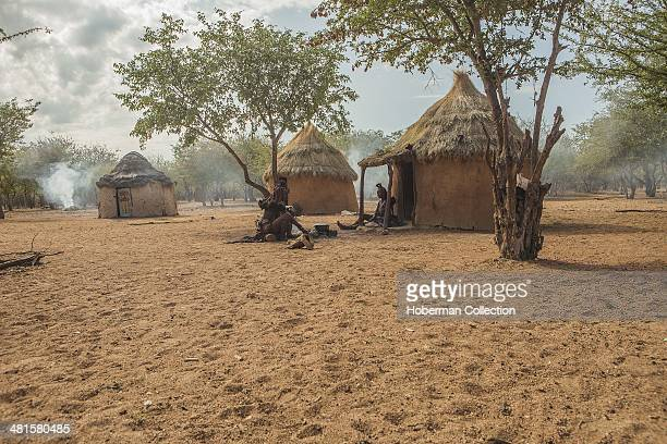 Traditional Himba Village With Huts and Working Himba Woman