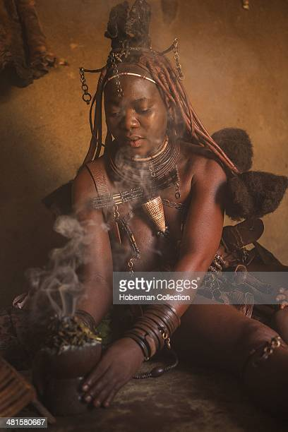 Traditional Himba Woman With Her Boy Preparing Traditional Medicine