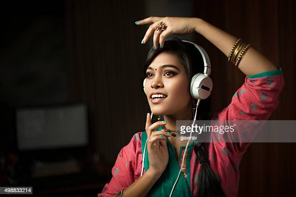Traditional Hindu teenage girl listening music through headphone and dancing.