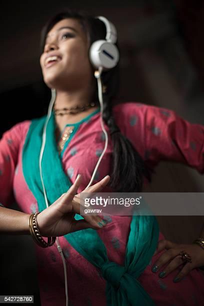 Traditional Hindu teenage girl listening music through headphone and dancing.