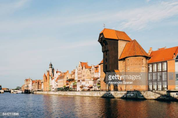 traditional historic houses and zuraw crane on motlawa river waterfront (dlugie pobrzeze) in gdansk, poland - motlawa river stock pictures, royalty-free photos & images